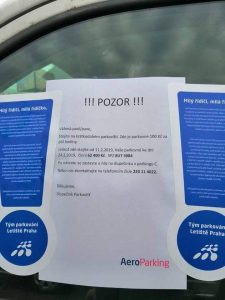 Výzva přilepená na auto zaparkované na Letišti Praha