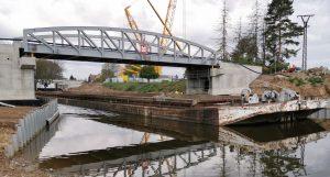 Osazování zdvižného železničního mostu v Lužci nad Vltavou (v pozadí). V popředí nový silniční most. Pramen: Ředitelství vodních cest
