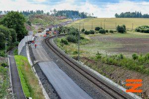 Znovu pohled k Sudoměřicím, tentokrát z nadjezdu silnice 1/3. Stávající trať se odklání, v oblouku je vidět zastávka Mezno, která se přesune blíž k obci. Pramen: Správa železnic