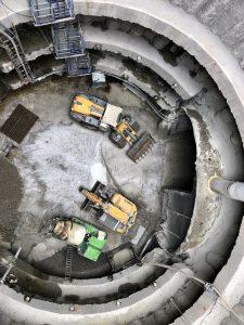 Podhled z přepravní klece zpod ramena jeřábu do 36 metrů hluboké těžební šachty v lokalitě VO-OL. Na dně šachty: nakladač rubaniny, tunelobagr a domíchávač betonu. Foto: Daniel Šabík / DPP